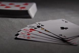 Fünf Spielkarten liegen neben einem Kartendeck auf einem Tisch.