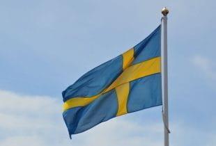 Schwedische Flagge im Wind vor bewölktem Himmel.