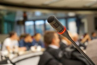 Ein Mikrofon an einem Rednerpult in einem mit Zuhörern besetzten Konferenzraum.