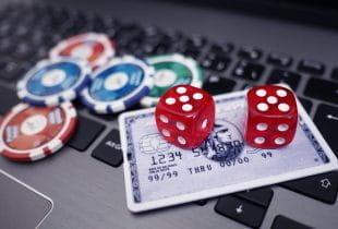 Auf der Tastatur eines Laptops liegen eine Kreditkarte, mehrere Pokerchips sowie zwei Würfel.
