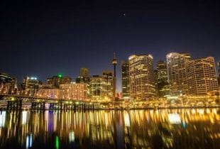 Hell beleuchtete Skyline der Stadt Sydney in Australien bei Nacht.