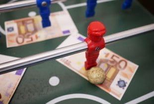 Rotes Kickermännchen mit Ball im Tischfußball stehend auf 50-Euro-Schein.