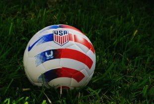Fußball im US-amerikanischen Design liegt auf grünem Rasen.