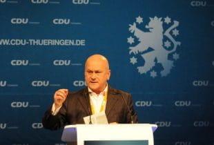 Abgeordneter der CDU hält eine Rede am Rednerpult und gestikuliert.