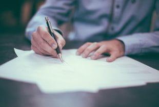 Mann unterzeichnet einen Vertrag mit Kugelschreiber.