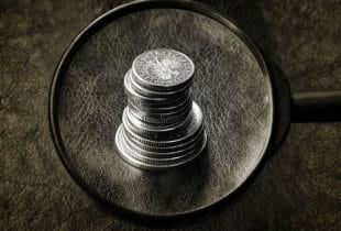 Eine Lupe hebt einen Stapel Münzen auf einem Ledertisch hervor.