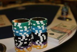 Zwei Stapel Pokerchips und ein Bündel Geldscheine auf einem Pokertisch.
