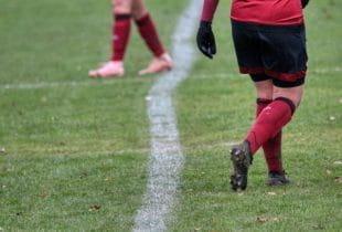 Beine zweier Fußballspieler auf grünem Fußballrasen.
