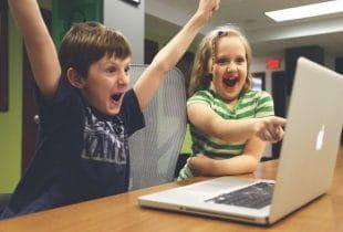 Zwei Kinder freuen sich vor einem Laptop.