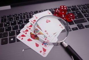 Auf einem Laptop liegen mehrere Würfel sowie verschiedene Spielkarten mit einer Lupe darauf.