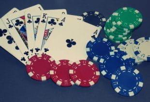 Die Spielkarten 10, Bube, Dame, König und Ass in Kreuz neben Pokerchips.
