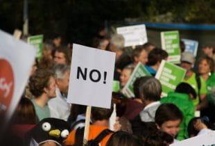 Protestbewegung mit einem No-Schild im Vordergrund.