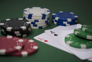 Spielkarten und Jetons auf grünem Untergrund.