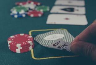 Ein Mann schaut sich sein Pokerblatt an.
