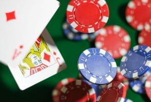 Zwei Spielkarten und mehrere Pokerchips fallen auf einem Pokertisch.