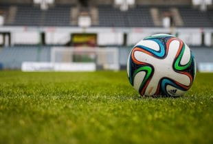 Fußball auf dem Rasen eines leeren Stadions.
