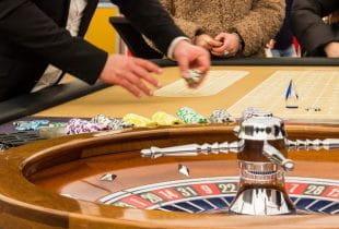 Roulette-Tisch mit Croupier und Spielern in einem Casino.