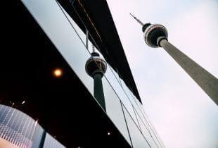 Der Berliner Fernsehturm spiegelt sich in einer gläsernen Hausfassade.
