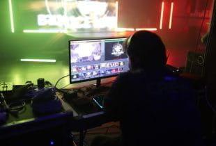 Person sitzt vor einem Rechner und streamt in einem beleuchteten Raum.