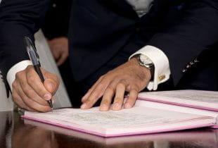 Ein Mann im Anzug unterschreibt einen Vertrag.