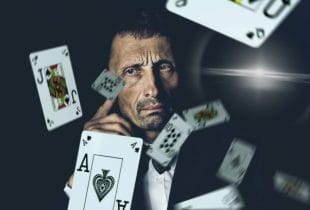 Pokerkarten fliegen vor einem nachdenkenden Mann umher.
