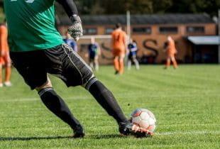 Torhüter schießt einen Ball während einer Fußballpartie.