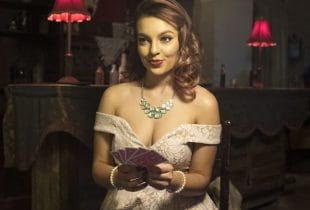Eine gut gekleidete Dame hält Pokerkarten in ihren Händen.