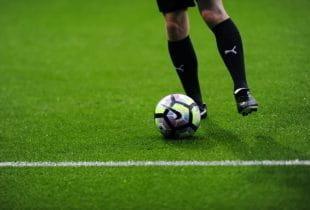 Fußballspieler mit Ball auf einer Rasenfläche.