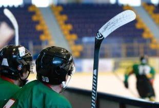 Zwei Eishockeyspieler verfolgen eine Partie vom Seitenrand.