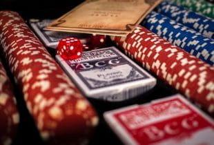 Würfel, Jetons und Spielkarten aufgereiht in einem Pokerkoffer.