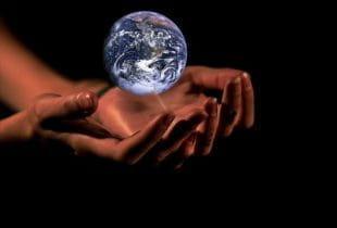 Über zwei Händen schwebt eine Weltkugel.