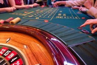 Mehrere Menschen sitzen an einem Roulette-Tisch.