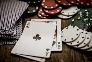 Spielkarten und Jetons auf Holzuntergrund.