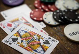 Spielkarten, Jetons und Dealer-Button auf Holzuntergrund.