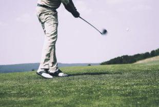 Ein Golfer schlägt mit einem Eisen einen Golfball.