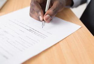 Ein Mann schreibt mit einem Stift auf einem Papier.