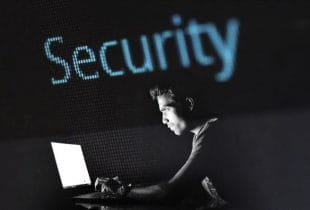 Ein Mann sitzt in einem dunklen Raum vor einem Laptop.