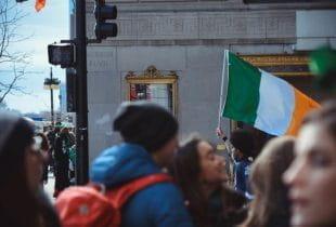 Ein Mann hält in einer Menschenmenge eine irische Flagge in den Händen.