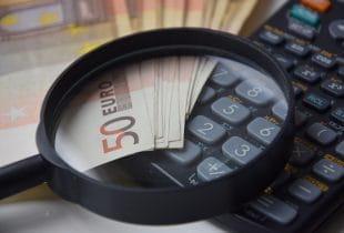 Mehrere Geldscheine, ein Taschenrechner und eine Lupe.