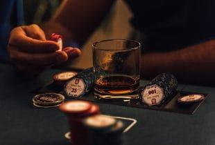 Ein Mann sitzt mit Jetons und einem Glas Scotch am Pokertisch.