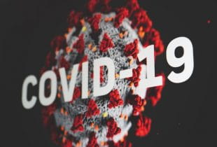 Covid-19-Schriftzug mit illustriertem Virus im Hintergrund.