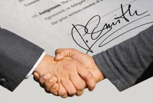 Zwei Männer schütteln sich die Hände vor einem Vertrag im Hintergrund.