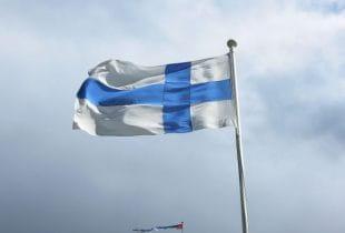 Die Flagge Finnlands weht an einem Mast im Wind.