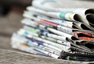 Ein Stapel Zeitungen auf einem hölzernen Untergrund.