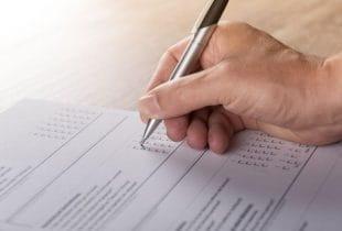 Eine Person füllt einen Umfragebogen aus.