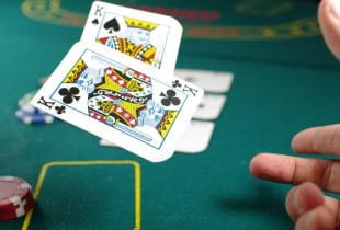 Eine Person wirft zwei Kreuz-Könige auf einen Pokertisch.
