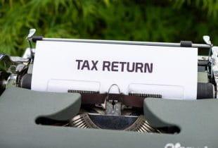 Ein Blatt in einer Schreibmaschine mit der Aufschrift tax return.